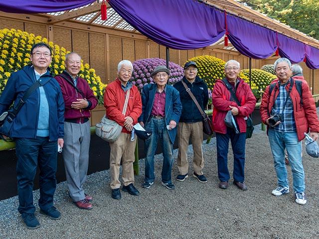 菊花壇の前に立つシニア男性