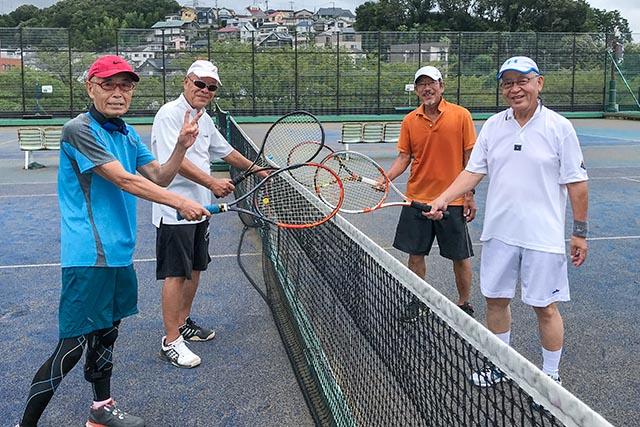 テニスコートに立つシニア男性